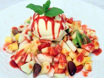 Фруктовий салат з ананасом, персиками, полуницями, сливами та бананами та морозивом