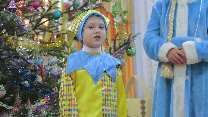 Мальчик раасказывает стих возле елки